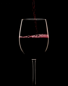 Red Wine being poured on a black background